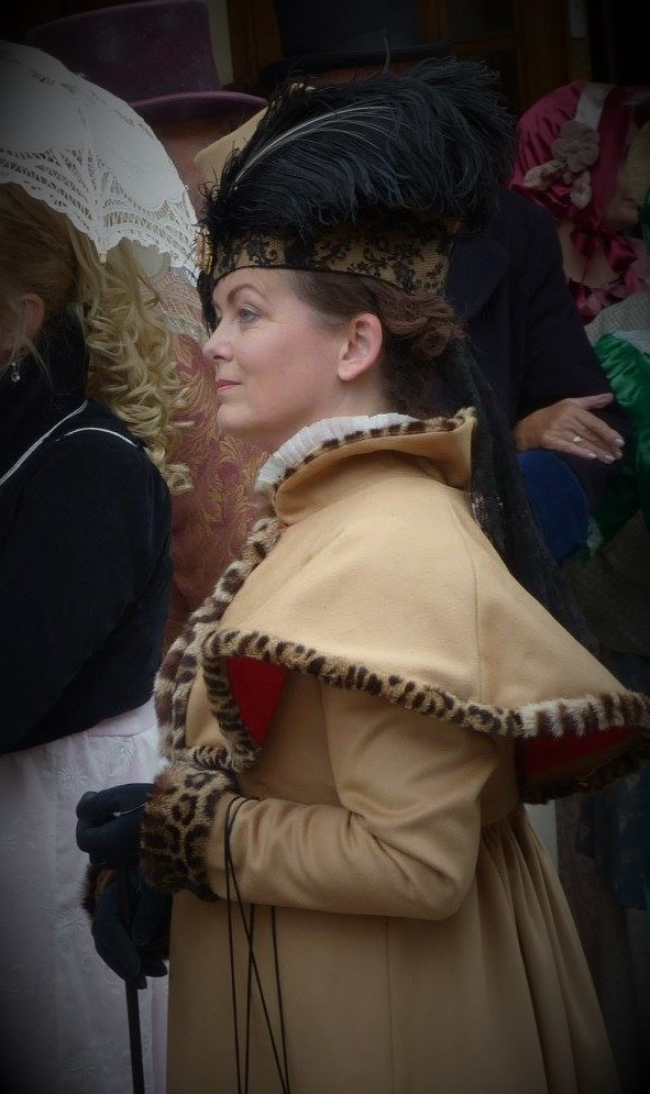 Regency Lady in a fawn coloured full length walking coat, with cape and matching hat.